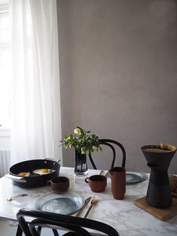 Morgenbord med spejlæg og kaffe og blomster i smuk vase på bordet