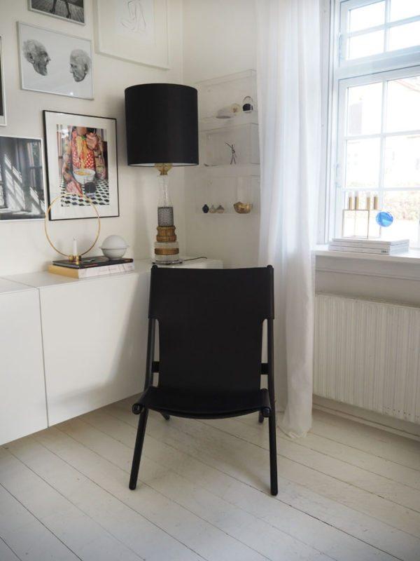 Et hjørne i en stue står en loungestol i sort læder foran en væghængt hvid skænk. På skænken står en overdådig krystal lampe med sort skærm og på væggen hænger utallige art prints