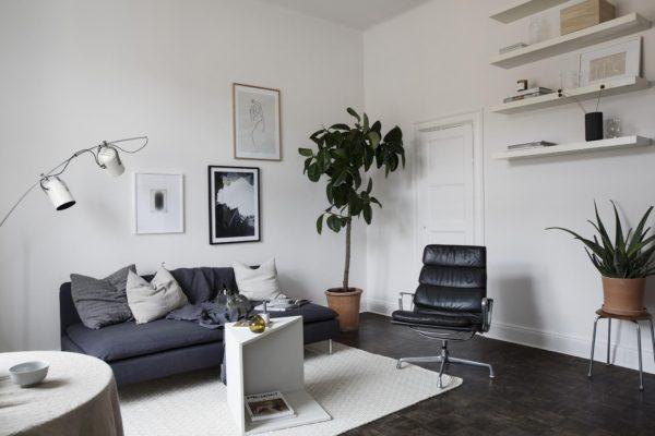 Her ses en stue med en grå to-personer sofa, en læder loungestol, og man kan lige ane lidt af en rundt spisebord. På væggen hænger tre billeder og i hjørnet stå et træ
