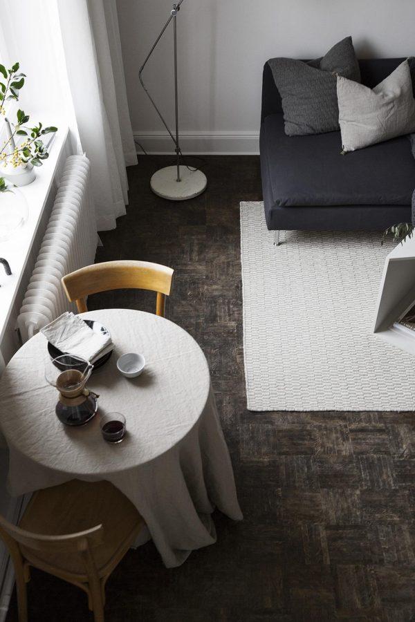 Billede af et hjørne af en stue taget oppe fra. Rundt spisebord med hørdug på og hjørnet af en grå sofa uden armlæn.