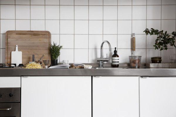 Her ses et køkken med hvide slagterfliser, hvide skabslåger og stål bordplade. Her er fuld gang i madlavningen