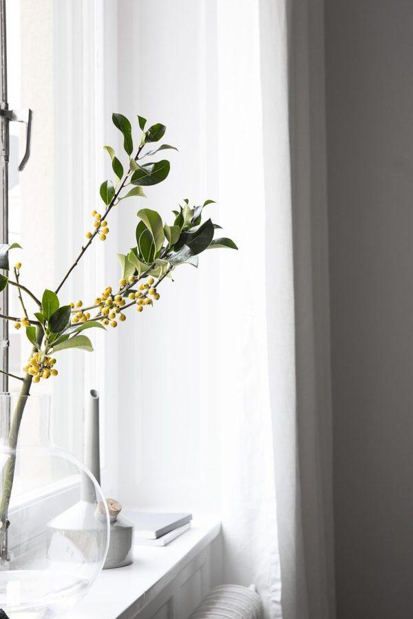 Stilleben i vindueskarmen. En stor glasvast med en gren i, en oliekande i grå porcelæn med skulpturel form og en stak magasiner