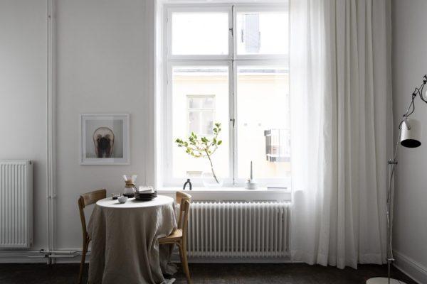 Her ses en fin spisplads i en stue. Et meget lille rundt bord med to stole omkring. På bordet ligger en sandfarvet hør-dug og i baggrunden ses vnduer omkranset af lyse gardiner som går fra gulv til loft.