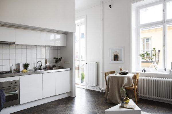 En et-værelses lejlighed med køkken, spiseplads og stue i et. Her ses køkkenafdelingen og den lille hyggelige spiseplads med det runde bord og 2 stole omkring