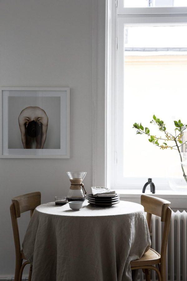 Her ses en fin spisplads i en stue. Et meget lille rundt bord med to stole omkring. På bordet ligger en sandfarvet hør-dug. På væggen hænder fotokunst i ramme.