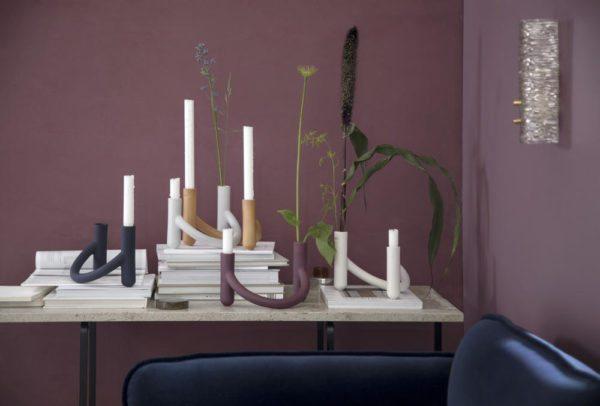 Her ses fem Nellemann stager i forskellige farver fra Kähler placeret på et bord i en violet stue