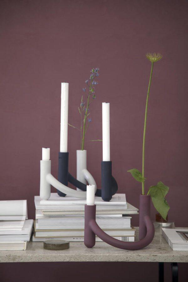 Tre stager i forskellige farver. Stagerne i keramik hedder Nellemann og er fra Kähler. De stå placeret i niveauer på stakke af magsiner op af en blommefarvet væg