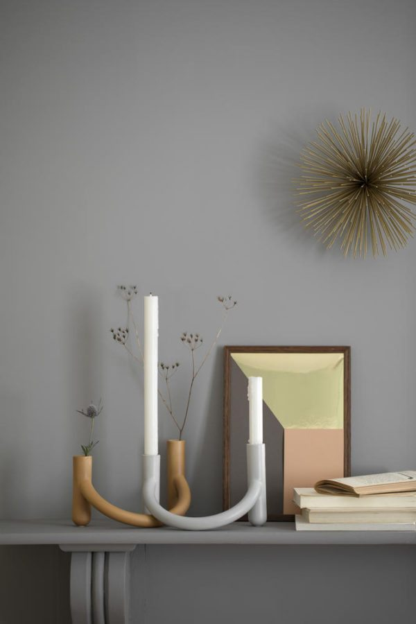 På en grå hylde op af en grå væg står to stk. Nellemann stager, den ene med lys og den anden med blomster i.