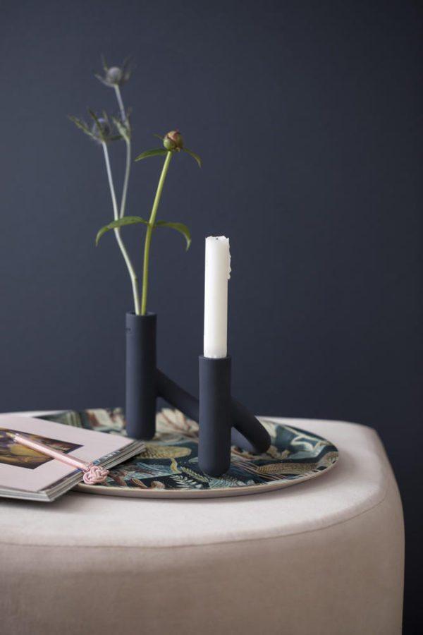 En rosa puf med en bakke placeret ovenpå. På bakken står en Nellemand stage/vase fra Kähler.