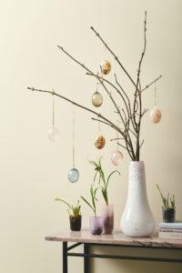 Påskepynt. En flot rosa vase med friske grene fra haven dekoreret med mundblæste glas påskeæg.